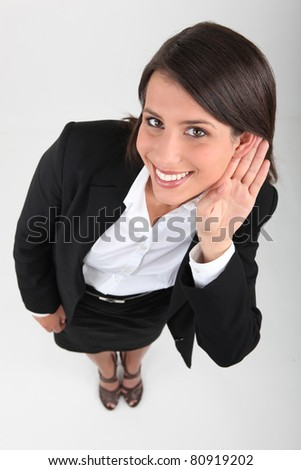 Businesswoman with hand to ear - stock photo