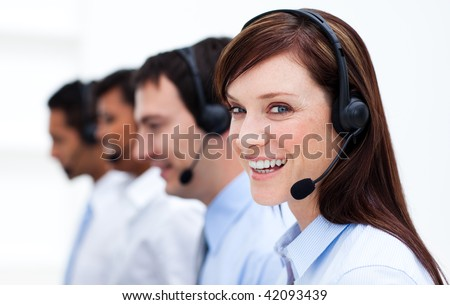 Businesswoman with headset on smiling at the camera in a call center - stock photo
