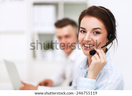 Businesswoman with headset smiling at camera in call center - stock photo