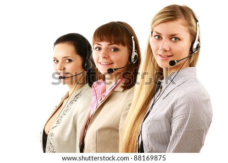 Businesswoman with headset smiling at camera in call center. Businessmen in headsets on background - stock photo