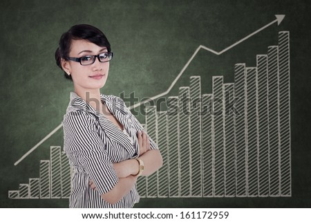Businesswoman with her arms crossed on growth graph background - stock photo