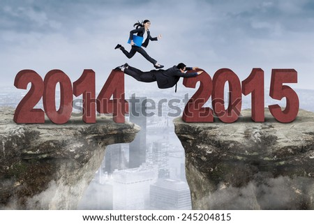 Businesswoman with her partner work together through a gap from number 2014 to 2015 - stock photo