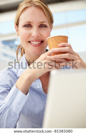 Businesswoman with laptop and coffee - stock photo