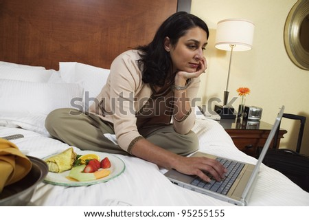 Businesswoman with laptop and food on hotel bed - stock photo