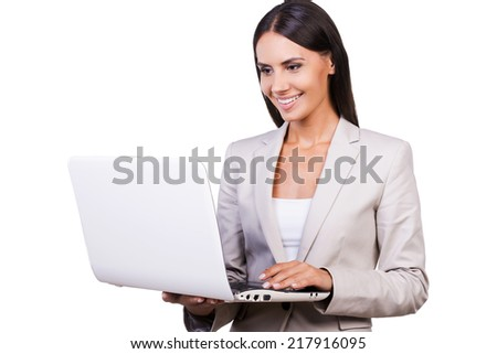 Businesswoman with laptop. Confident young businesswoman in suit working on laptop while standing isolated on white background