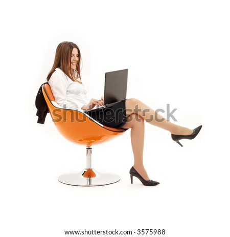 businesswoman with laptop in orange chair over white - stock photo