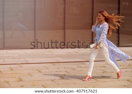 Businesswoman with long brown hair speaking over smart phone and hurrying up. Lady with blue coat on walking along the office building. Toned image. - stock photo
