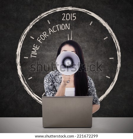 Businesswoman with megaphone and the word time for action in 2015 on the blackboard - stock photo