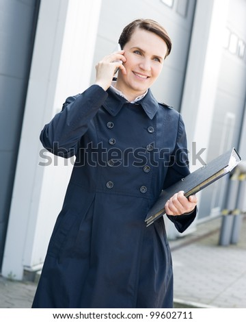 Businesswoman with mobile phone and file folder in front of warehouse
