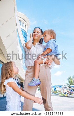 Businesswoman with mobile phone and kids - stock photo