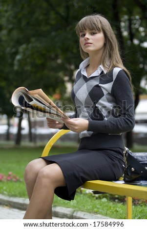 businesswoman with newspaper in park - stock photo