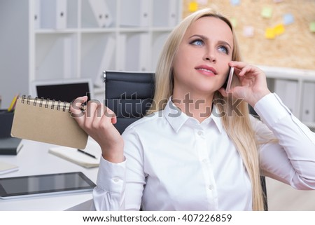 Businesswoman with notepad talking on the phone - stock photo