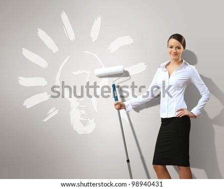 Businesswoman with paint brush and green energy symbols - stock photo