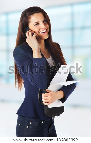 Businesswoman with papers and talking on smart phone at office. Young business woman - stock photo