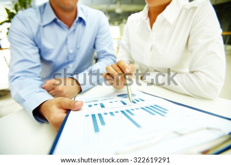 Businesswoman with pen explaining data to colleague - stock photo