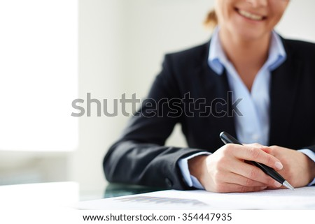 Businesswoman with pen over documents