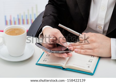 Businesswoman with phone, calendar and a coffee