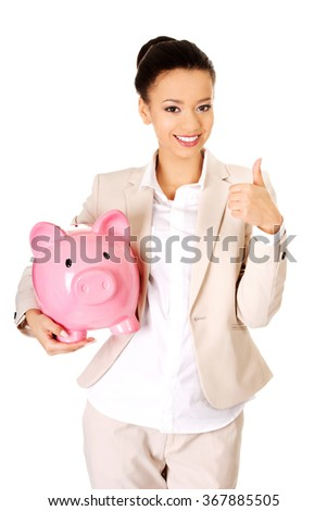 Businesswoman with piggybank and thumbs up.