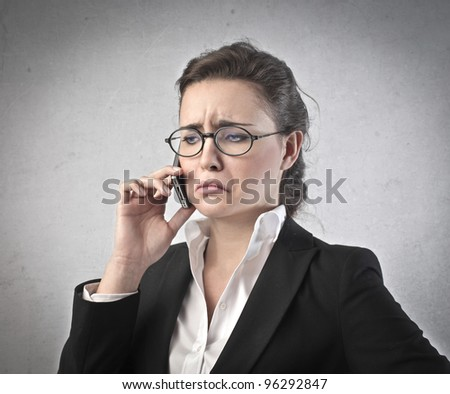 Businesswoman with sad expression talking on the mobile phone - stock photo