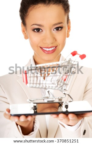 Businesswoman with shopping cart and tablet. - stock photo