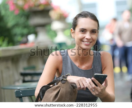 Businesswoman with smartphone in park, waiting for someone