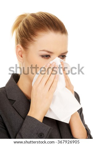 Businesswoman with sneezing into tissue.