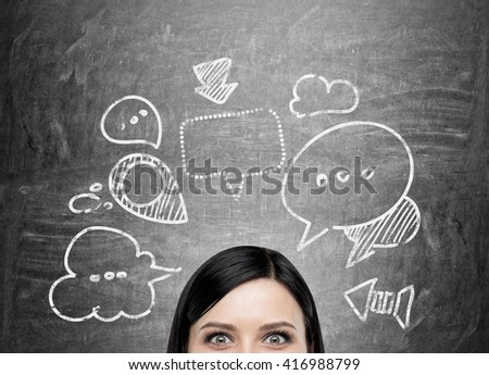 Businesswoman with speech and thought bubbles on chalkboard - stock photo