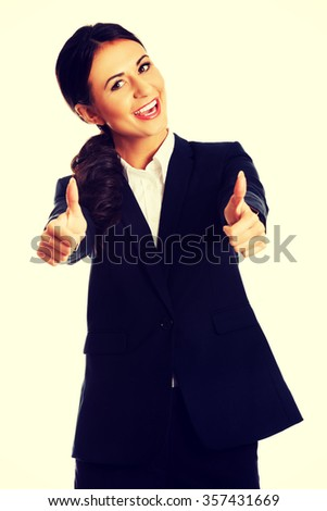 Businesswoman with thumbs up gesture. - stock photo