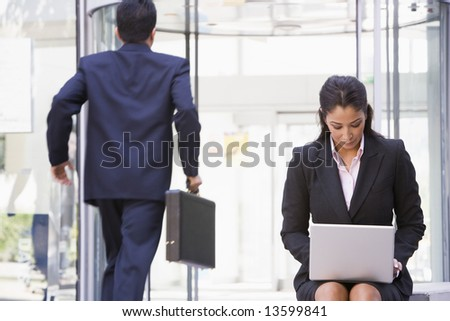 Businesswoman working at laptop outside office - stock photo