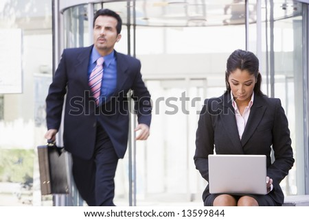 Businesswoman working at laptop outside office building - stock photo
