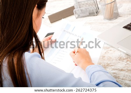 Businesswoman working at the office with the laptop and some documents
