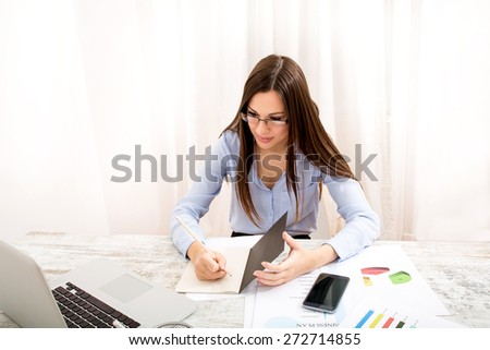 Businesswoman working at the office with the laptop and some documents - stock photo