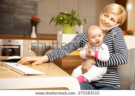 Businesswoman working from home, holding baby girl on lap. - stock photo