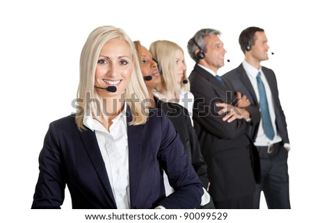 Businesswoman working in a call center with her team in background looking away - stock photo