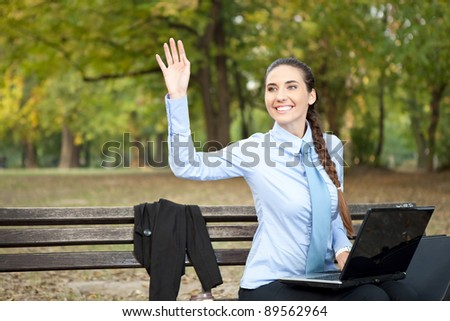 businesswoman working in park and waving hello - stock photo