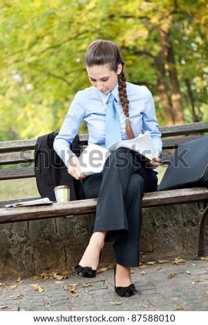 businesswoman working in park on break - stock photo