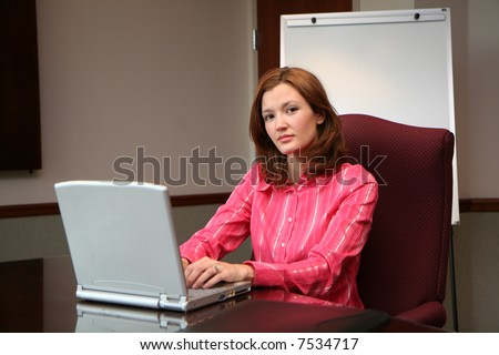 Businesswoman working on a computer in a conference room - stock photo