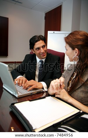 Businesswoman working on a computer in an office with coworker - stock photo
