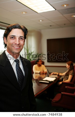 Businesswoman working on a computer in an office with coworker standing in foreground - stock photo