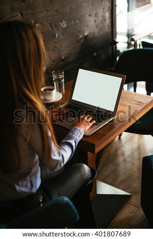 Businesswoman working on a laptop in a cafe. - stock photo