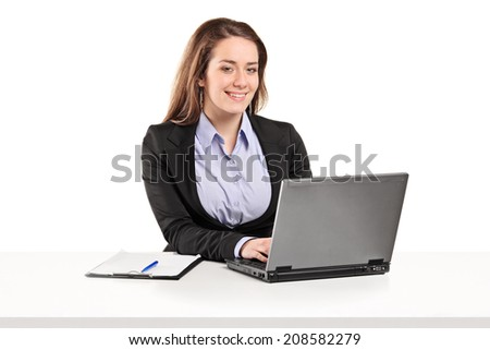 Businesswoman working on a laptop seated at a table isolated on white background - stock photo