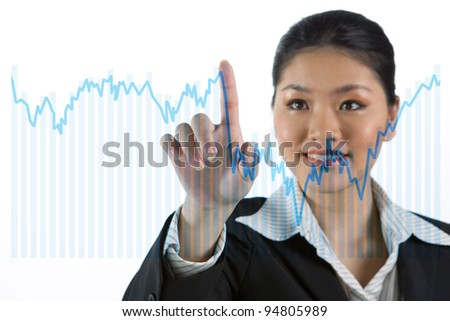 Businesswoman working on a virtual financial touch-screen. - stock photo