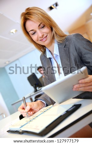 Businesswoman working on agenda and tablet