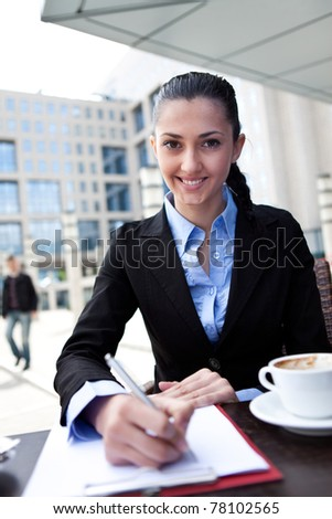 businesswoman working on coffee break in restaurant outdoor - stock photo