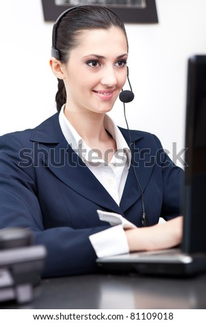 businesswoman working on computer with headset i office - stock photo