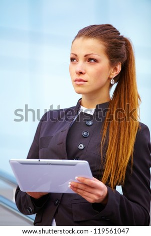 Businesswoman working on digital tablet outdoor over building background