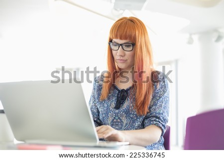 Businesswoman working on laptop in creative office - stock photo