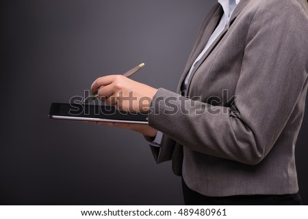 Businesswoman working on tablet computer in business concept