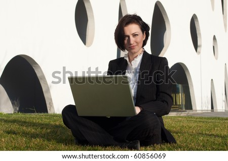 Businesswoman working with a laptop and sitting on the grass - stock photo