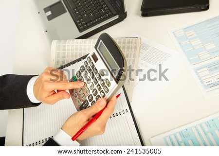 Businesswoman working with calculator in the office - stock photo